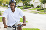 Man riding a bike while wearing a helmet represents interventions to increase physical activity.