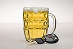 Mug of beer next to car key and fob represents sobriety checkpoint programs to reduce alcohol-impaired driving.