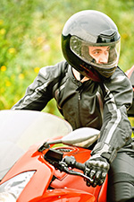 Man on motorcycle, wearing helmet represents universal helmet laws to prevent motor vehicle deaths and injuries.