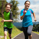 adolescent children running for exercise on an outdoor pathway.